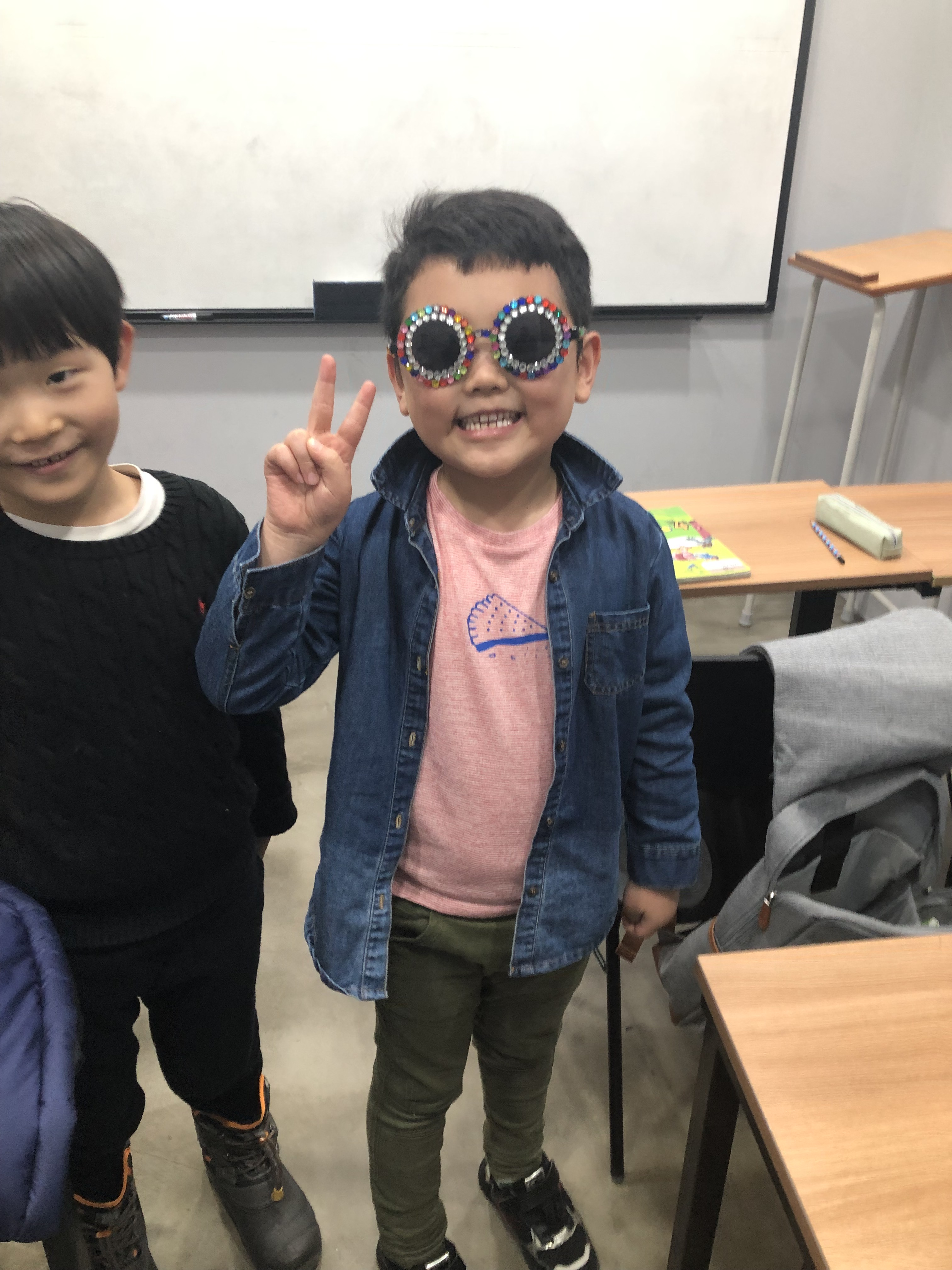 student in classroom making peace sign